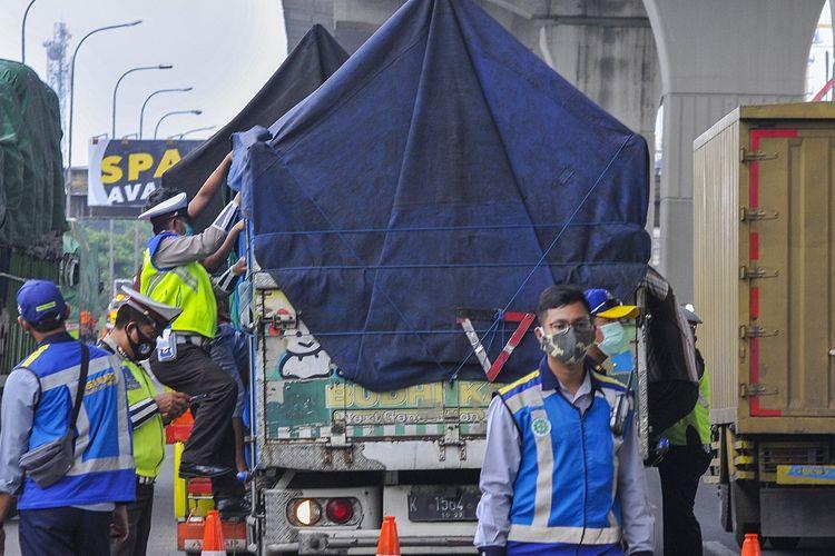 Petugas kepolisian memeriksa muatan truk yang melintas di tol Jakarta-Cikampek di Cikarang Barat, Kabupaten Bekasi, Jawa Barat, Sabtu (2/5/2020). Menurut data Ditlantas Polda Metro Jaya, sebanyak 7.748 kendaraan dipaksa putar balik menuju lokasi asal akibat terjaring razia Operasi Ketupat 2020. ANTARA FOTO/Fakhri Hermansyah/wsj.