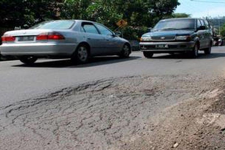 Salah satu segmen jalan di Tanjungsari, Sumedang, Jawa Barat, rusak parah, Kamis (9/5/2013). Kondisi jalan rusak itu ditemui mulai dari Majalengka hingga Sumedang. Padahal, jalur itu menghubungkan dua pusat kegiatan nasional (PKN), yakni Cirebon dan Bandung. Kerusakan jalan itu mengakibatkan sopir menambah biaya untuk membeli bahan bakar minyak (BBM) dan memakan waktu pengiriman barang serta penumpang yang lebih lama.