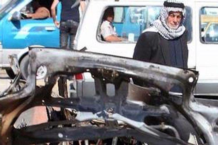 Seorang warga Irak melewati sebuah mobil yang hancur di lokasi ledakan kota Sadr, sektar Baghdad.