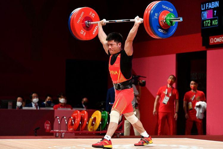 Aksi lifter China Li Fabin yang turun di kelas 61 kilogram putra cabang olahraga angkat besi Olimpiade Tokyo 2020, 25 Juli 2021.