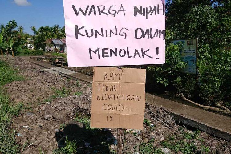 Spanduk dan plang penolakan warga terkait rencana Pemerintah Kota Pontianak, Kalimantan Barat, menjadikan Rusunawa Nipah Kuning sebagai tempat isolasi pasien dalam pengawasan (PDP) dengan gejala ringan dan asimptomatik atau orang tanpa gejala (OTG).