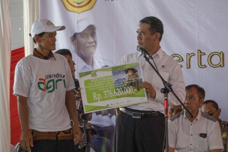 Menteri Pertanian Andi Amran Sulaiman memberikan bantuan Asuransi Usaha Tani Padi (AUTP) kepada petani