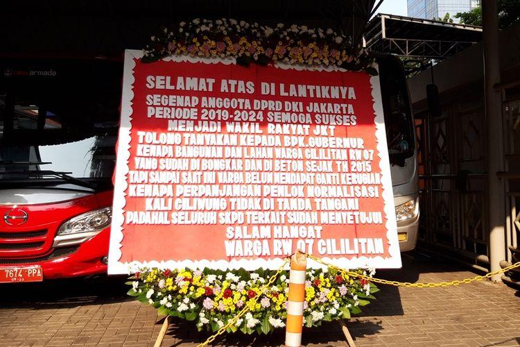 Karangan bunga dari warga RW 07, Cililitan, Jakarta Timur yang memberikan ucapan selamat atas pelantikan DPRD DKI dan menyindir Gubernur DKI Jakarta Anies Baswedan terkait ganti rugi normalisasi, di Gedung DPRD DKI, Jalan Kebon Sirih, Jumat (30/8/2019)