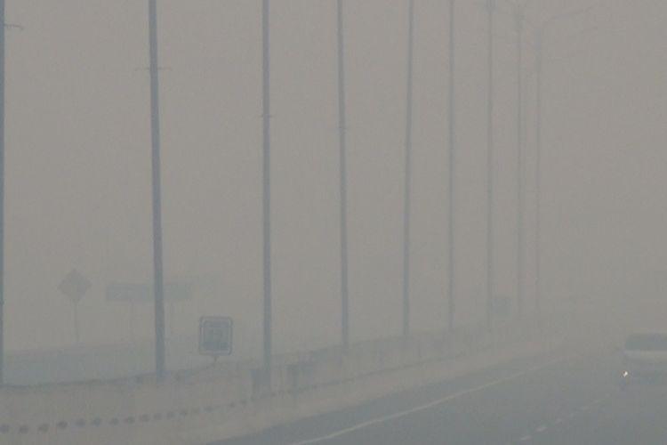 Jalan tol Palindra diselimuti kautvasap tebal sehingga jarak pandang menjadi terbatas. Kendaraan yang melintas nyaris tak terlihat tertutup kabut asap, Selasa (15/10/2019).