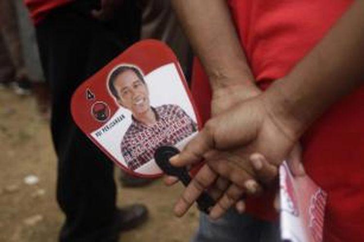 Simpatisan membawa kipas bergambar Joko Widodo atau Jokowi, saat calon presiden yang juga Gubernur DKI Jakarta tersebut menjadi juru kampanye PDI-P di lapangan Papua Trade Center, Jayapura, Papua, 5 April 2014. Jokowi juga menyempatkan diri untuk berkunjung ke pasar Yotefa di Abepura.