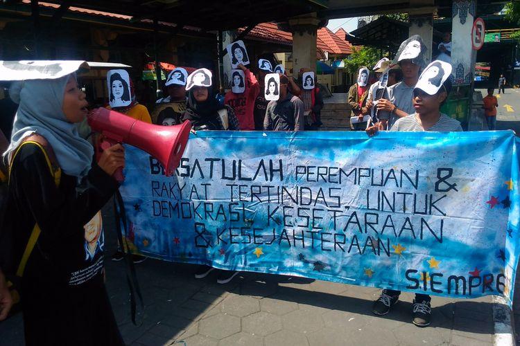 Sejumlah mahasiswa yang tergabung dalam Serikat Pembebasan Perempuan (Siempre) memakai topeng berwajah Marsinah di Jalan Malioboro, Kota Yogyakarta, Senin (8/5/2017)