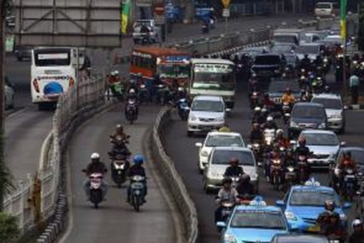 Pengendara melintas di jalur bus Tansjakarta di kawasan Mampang, Jakarta Selatan, Selasa (29/10/2013). Dirlantas Polda Metro Jaya akan menerapkan denda bagi pengendara yang menerobos jalur bus sebesar Rp 1 juta bagi kendaraan roda empat dan Rp 500.000 bagi kendaraan roda dua.