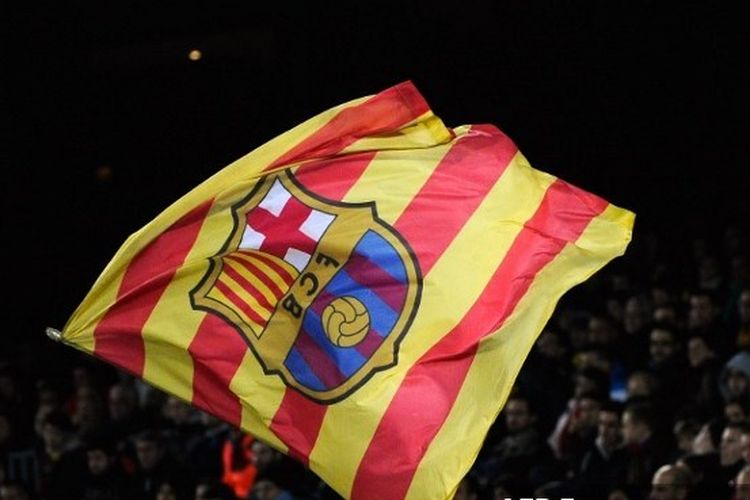 Suporter FC Barcelona mengibarkan bendera