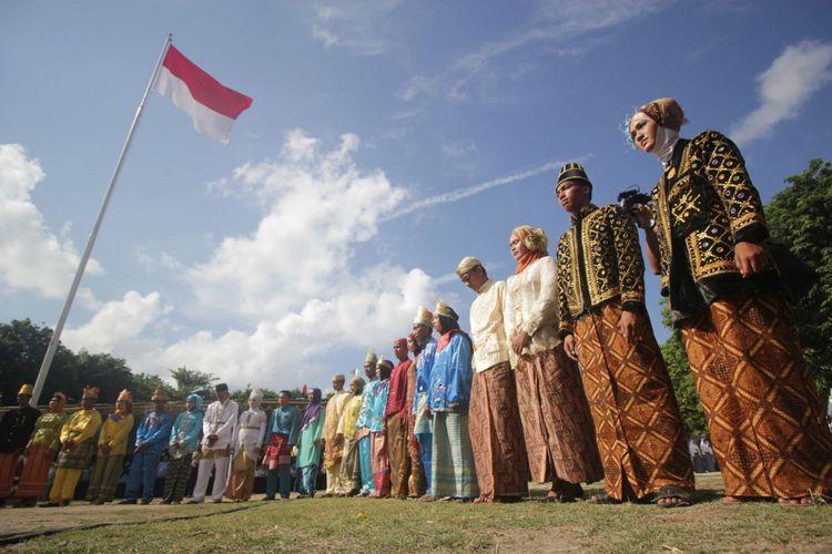 Sejumlah pemuda memakai pakaian adat saat mengikuti upacara bendera di Pulau Bawean, Gresik, Jawa Timur, Sabtu (28/10/2017). Upacara dengan pakaian adat tersebut dalam rangka memperingati Hari Sumpah Pemuda.