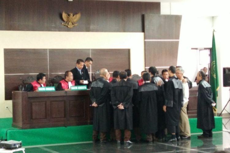 Tim Jaksa Penuntut Umum bersama tim penasihat hukum Buni Yani saat berdiskusi di meja majelis hakim dalam persidangan kasus pelanggaran ITE di Gedung Dinas Perpustakaan dan Kearsipan (Dispusip) Kota Bandung, Jalan Seram, Kota Bandung, Selasa (26/9/2017)