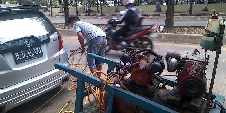 Penyedia jasa tambal ban dari Jalan Sriwijaya 4 sengaja dipanggil ke Jalan Raden Patah 1 untuk memasang pentil dan memompa ban kendaraan yang digembosi dalam penertiban parkir liar di kawasan Kebayoran Baru, Jakarta Selatan, (7/10/2013).