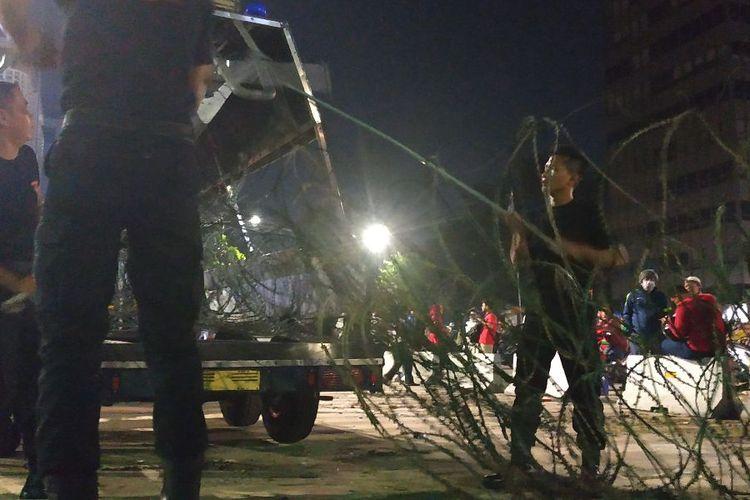 Anggota Brimob menggeret barikade kawat berduri yang rusak di depan Sarinah, Kamis (23/5/2019) malam.