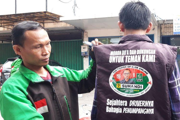Suhandi, pengendara ojek online yang jadi caleg DPR RI dari PKB saat menunjukan rompi kampanye