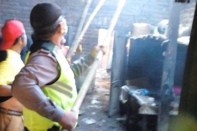Petugas memadamkan api yang membakar rumah kios di Kecamatan Bungkal, Ponorogo.