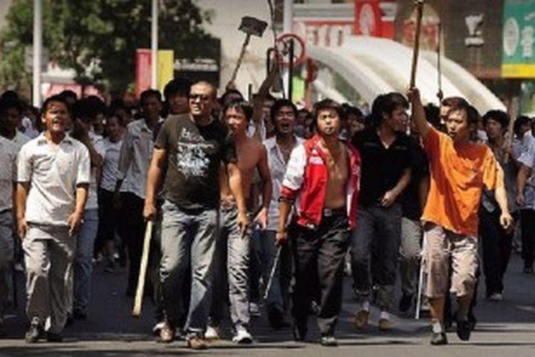 Kerusuhan di Provinsi Xinjiang, China bagian barat, Rabu (26/6/2013), menyebabkan 27 orang tewas. Dalam foto di atas, warga China etnis Han berpawai dalam bentrokan antara etnis di daerah itu tahun 2009.