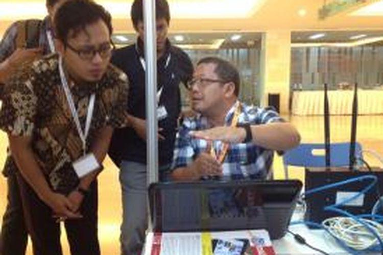 Onno W. Purbo (paling kanan) sedang menjelaskan cara mengoperasikan OpenBTS kepada pengunjung Internet Governance Forum (IGF) 2013 di Bali Nusa Dua Convention Center, Bali, Selasa (22/10/2013).