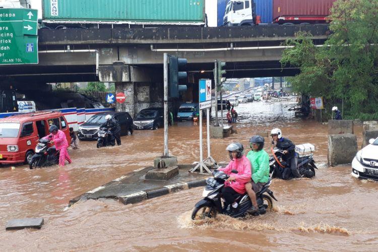 Tampak Banjir setinggi lutut orang dewasa menggenang di kolong Tol JORR Jalan KH.Noer Ali, Bekasi Barat, Kota Bekasi, Senin (26/11/2018).
