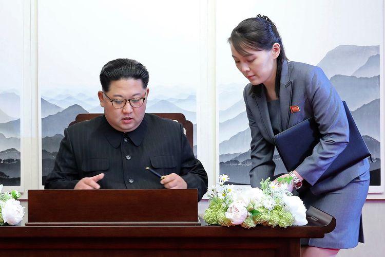 Foto yang dirilis pada 27 April 2018 memperlihatkan, Pemimpin Korea Utara Kim Jong Un menandatangani buku tamu di sebelah adik sekaligus penasihatnya, Kim Yo Jong, di desa perbatasan terpercaya Panmunjeom, Korea Selatan.