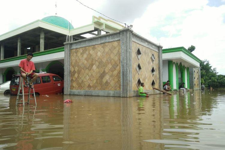 Warga RT 1 RW 17 di Perumahan Citra Villa Wanasari, Cibitung, Kabupaten Bekasi memancing di tengah gempuran banjir.