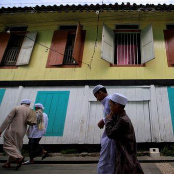 Warga Palembang keturunan Arab pulang seusai menjalankan ibadah Sholat Idul Fitri di Musholah Kampung Al-Munawar, Kecamatan Seberang Ulu II, Palembang, Sumatera Selatan, Minggu (25/6/2017).