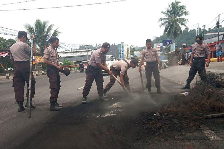 Sejumlah polisi membersihkan sisa kerusuhan di salah satu ruas jalan di Manokwari, Papua Barat, Selasa (20/8/2019). Kondisi Manokwari sudah kondusif dan warga mulai melakukan aktivitas di ruang publik meskipun dalam skala terbatas.