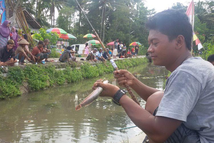 Warga tumpah ruah ke pinggiran selokan yang membelah dusun mereka Dusun Kanoman, Desa Kulwaru, Kecamatan Wates, Kulon Progo, DI Yogyakarta. Mereka memancing bebas ikan lele yang berlimpah di saluran pembuangan  maupun irigasi sawah ini.