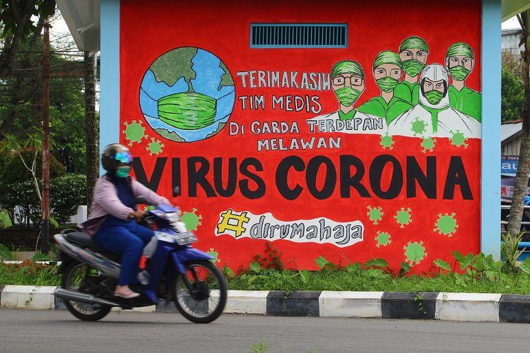 Seorang pengendara motor melintas di depan mural tentang pandemi COVID-19 di Pontianak, Kalimantan Barat, Kamis (29/4/2021). Mural yang dibuat oleh warga setempat itu untuk memberikan dukungan atas perjuangan tim medis yang selama ini berada di garis terdepan dalam penanganan COVID-19 khususnya di Pontianak. ANTARA FOTO/Jessica Helena Wuysang/wsj.