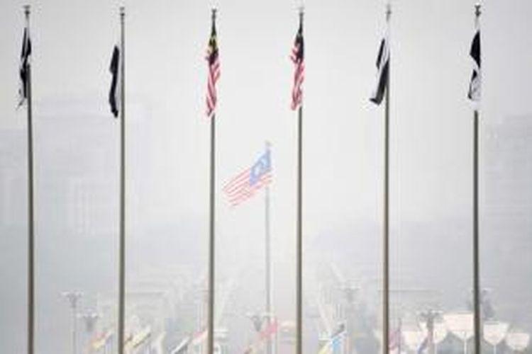 Bendera kebangsaan Malaysia berkibar diselimuti kabut asap di Putrajaya, 14 September 2015. Kabuat asap berasal dari kebakaran hutan dan lahan di Indonesia.