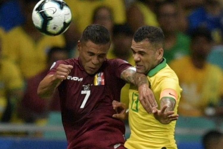 Bek timnas Brasil, Dani Alves, berusaha merebut bola yang disundul pemain Venezuela, Darwin Machis, pada laga Copa America di Fonte Nova Arena, Salvador, Brasil, 18 Juni 2019.