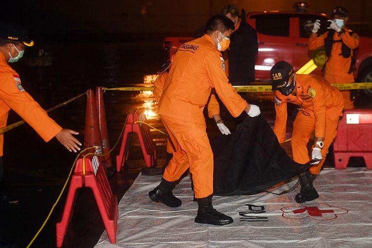 Petugas Basarnas membawa kantong berisi diduga serpihan dari pesawat Sriwijaya Air SJ 182 rute Jakarta - Pontianak yang hilang kontak di perairan Pulau Seribu, di Dermaga JICT, Jakarta, Sabtu (9/1/2021). Pesawat Sriwijaya Air SJ 182 hilang kontak di antara Pulau Laki dan Pulau Lancang pada Sabtu sekitar pukul 14.40 WIB atau 4 menit setelah lepas landas dari Bandara Soekarno Hatta, Tangerang.