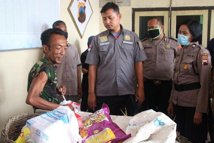 Kasat Reskrim Polres Karanganyar, AKP Ismanto Yuwono memberikan paket sembako kepada pemulung yang tertangkap karena mencuri padi di sawah di Karanganyar, Jawa Tengah.