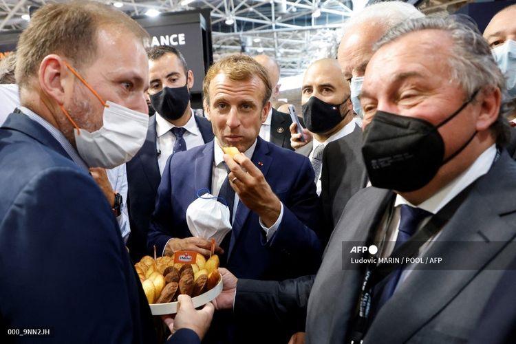 Presiden Perancis Emmanuel Macron (tengah) bersama Menteri Junior untuk Usaha Kecil dan Menengah Alain Griset mencoba produk Saint Michel di pameran internasional katering dan perhotelan (Sirha) di Eurexpo Hall di Lyon, Perancis, pada 27 September 2021.