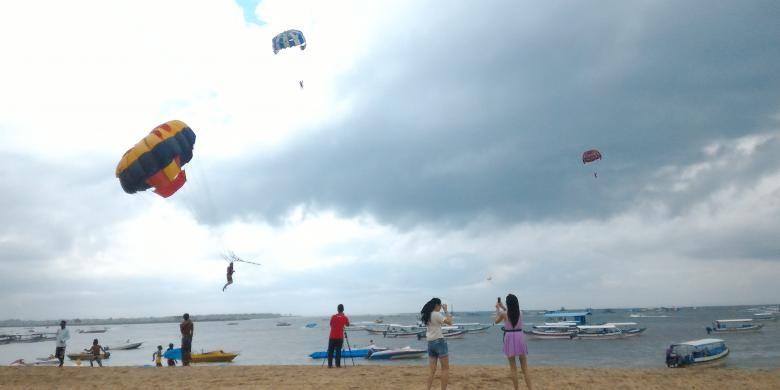 Wisatawan saat bermain parasailing di Pantai Tanjung Benoa