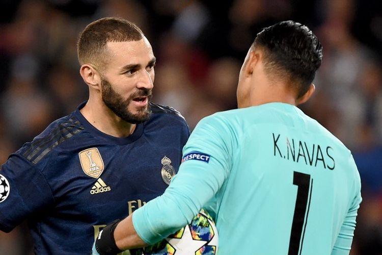 Karim Benzema berbincang dengan Keylor Navas pada sela-sela pertandingan PSG vs Real Madrid dalam matchday 1 Liga Champions di Parc des Princes, 18 September 2019.