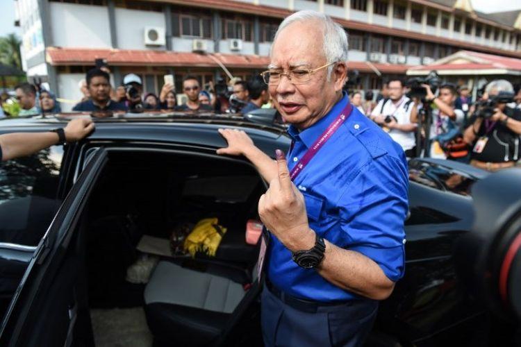 Perdana Menteri Malaysia Najib Razak menunjukkan jari yang terkena tinta, setelah memilih di tempat pemungutan suara di Pekan, Rabu (9/45/2018). (AFP/Mohd Rasfan)