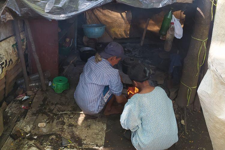 Tarso (70) dan pasangannya Sugiyani (31) memasak di dapur yang berada di belakang gubuk tempat tinggalnya di Kelurahan Kedungwuluh, Kecamatan Purwokerto Barat, Kabupaten Banyumas, Jawa Tengah.