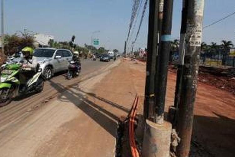 Ruas jalan inspeksi saluran Kalimalang di kawasan Duren Sawit, Jakarta Timur, yang sedang dilebarkan menyisakan jaringan utilitas di tengah jalan, Kamis (9/7). Jalan tersebut menjadi salah satu jalan utama bagi pemudik, khususnya pengendara sepeda motor, yang akan meninggalkan Jakarta.