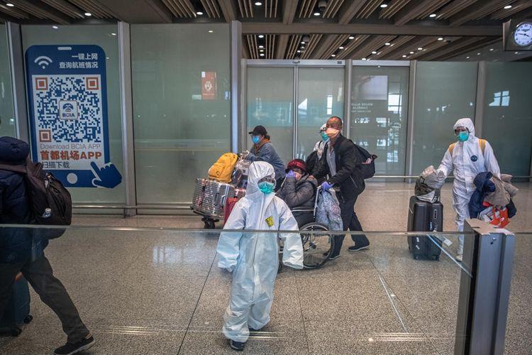 Para penumpang memakai masker dan pakaian pelindung di Beijing Capital International Airport, Beijing, China, 4 Maret 2020, untuk menghindari tertular virus corona.