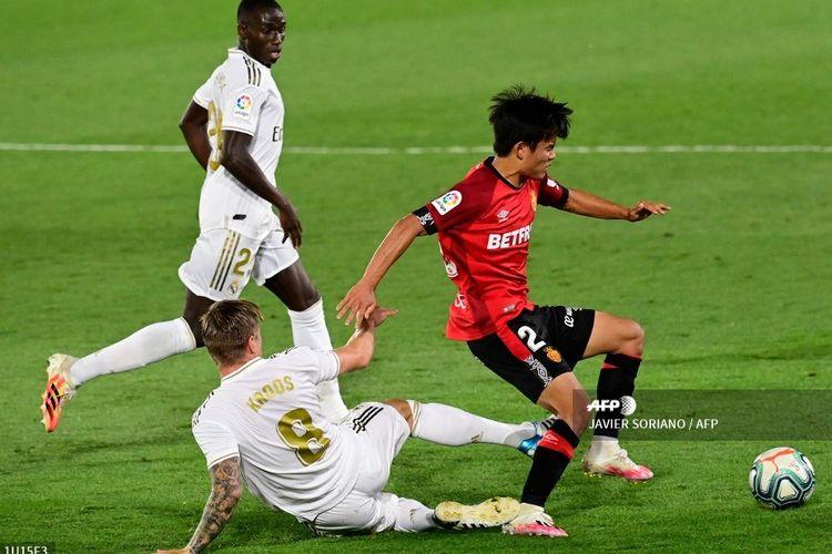 Takefusa Kubo beraksi melewati Toni Kroos pada laga Real Madrid vs Sevilla di Stadion Alfredo Di Stefano, Kamis (25/6/2020) dini hari WIB.