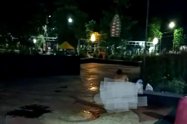 Wanita mandi telanjang bulat di alun-alun Kraksaan malam hari.