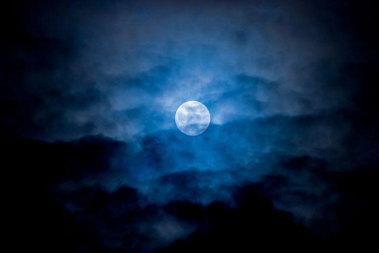 Ilustrasi blue moon atau bulan biru tertutup awan.