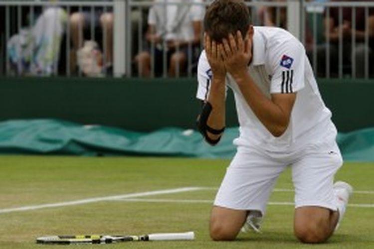 Petenis Polandia, Jerzy Janowicz , terduduk dan  menutup muka, setelah meraih kemenangan atas Jurgen Melzer dari Austria pada babak keempat turnamen Grand Slam WImbledon, Senin (1/7/2013).