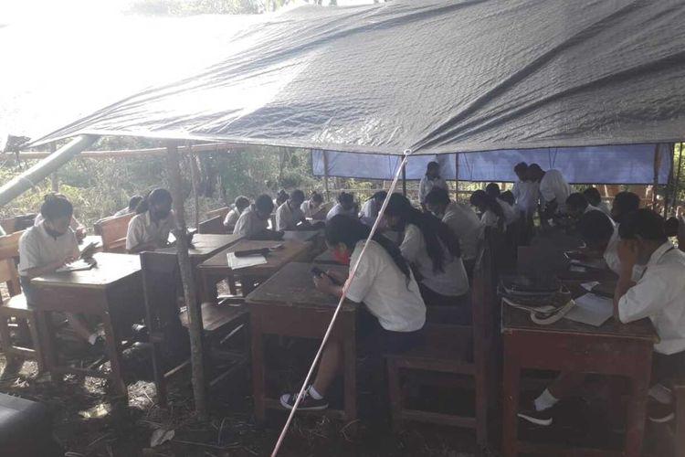 sebanyak 47 siswa dan siswi SMPN04 Kota Komba, Kabupaten Manggarai Timur, NTT mengikuti ujian try out di bawah tenda terpal di Puncak Wokonggoro, Desa Gunung, Kecamatan Kota Komba, Senin, (15/3/2021). jaringan sinyal internet hanya bisa di puncak bukit tersebut. (DOK/Fidelis Ambon-Kepsek SMPN04 Kota Komba)