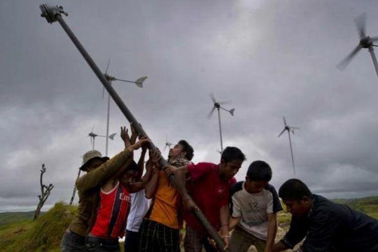 Warga bergotong-royong mendirikan kincir angin tambahan di kawasan turbin angin di Desa Kamanggih, Pulau Sumba, 19 Maret 2014.