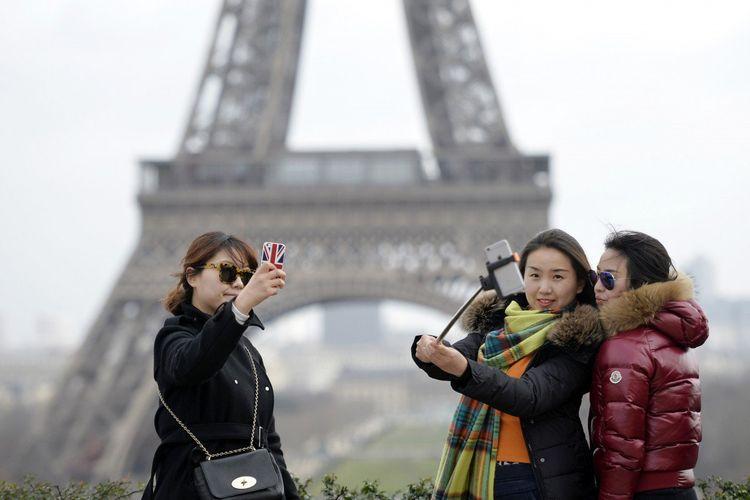 Tiga turis China tengah melakukan selfie dengan latar belakang Menara Eiffel di Paris, Perancis.
