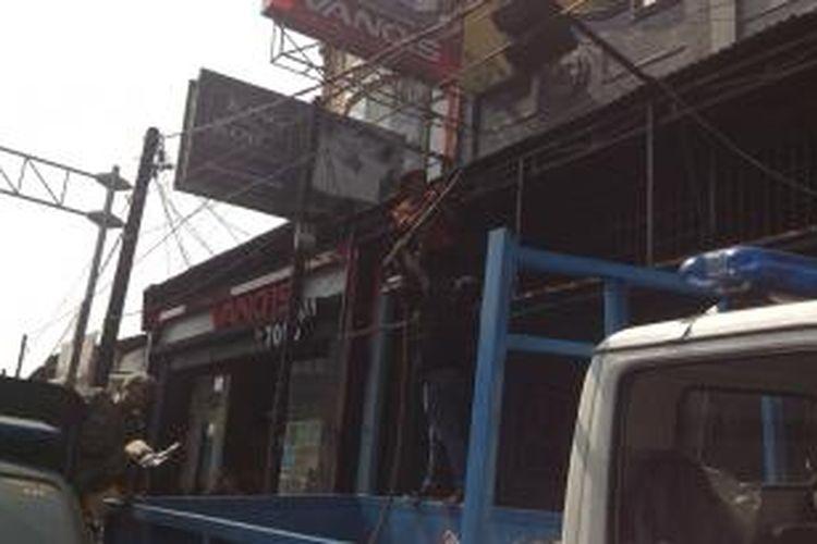 Petugas Satpol PP mencopot papan reklame di toko-toko sepanjang Jalan Raya Ragunan, Pasar Minggu, Rabu (11/9/2013). Penertiban dipimpin oleh Wali Kota Jakarta Selatan Syamsudin Noor dan melibatkan petugas gabungan dari Dinas Perhubungan, Dinas Perpajakan, Dinas Pekerjaan Umum, serta kepolisian setempat.