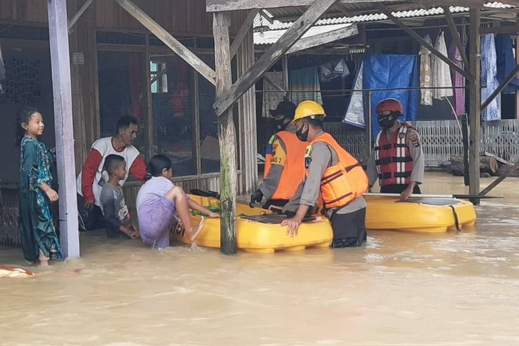 Tiga anggota polisi dari Polsek Satui terpaksa mengevakuasi warga yang terdampak banjir di Kecamatan Satui, Kalsel pada, Kamis (3/9/2020).