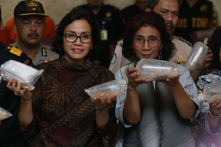Menteri Kelautan dan Perikanan Republik Indonesia Susi Pudjiastuti (kanan) dan Menteri Keuangan Sri Mulyani menunjukkan barang bukti saat rilis kasus penyelundupan bibit lobster di Gedung KPU Bea Cukai Tipe C Bandara Soekarno-Hatta Tangerang, Banten, Jumat (23/02/2018). Direktorat Jenderal Bea dan Cukai, Kementrian Keuangan, menggagalkan penyelundupan 71.982 ekor benih lobster jenis pasir dan mutiara di Terminal Keberangkatan 2D Bandara Soekarno-Hatta pada Kamis 22 Februari 2018 kemarin.