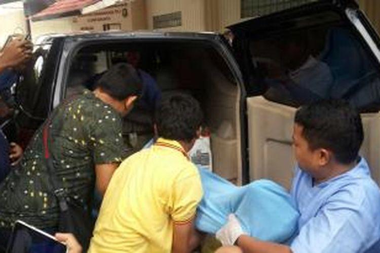 Petugas membawa jenazah ITH, pelaku pemerkosaan dan perampokan RJ (23) di Jembatan Penyebrangan Orang (JPO) Pondok Pinang, ke dalam kamar mayat RS Polri Kramat Jati, Jakarta Timur, Jumat (27/11/2015)