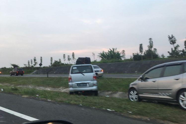 Pemudik menyeberangi parit untuk pindah ke jalur sebelahnya di ruas tol Cipali setelah seluruh ruas jalan di tol ini digunakan untuk kendaraan arah ke Jakarta, Sabtu (1/7/2017) petang.
